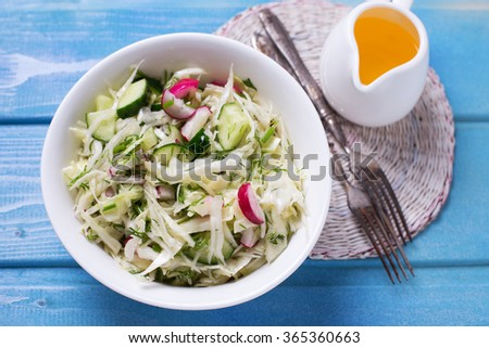 Salad from cabbage, herbs, cucumber, onion and radish in bowl on blue wooden background. Coleslaw.  Healthy eating. Selective focus. - stock photo