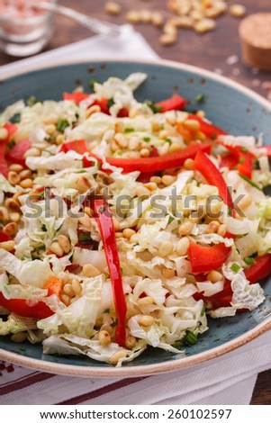 Salad from cabbage with red pepper and pine nuts..selective focus - stock photo