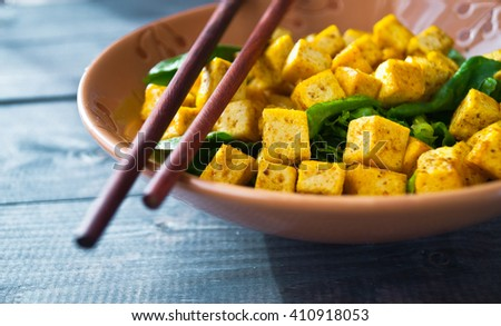 Salad from fried tofu with curry and fresh spinach in brown bowl with chopsticks as food background - stock photo