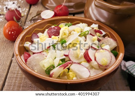 Salad from radish and egg in a ceramic bowl. - stock photo