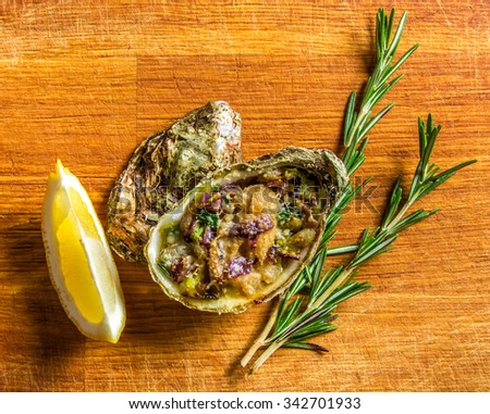 Salad in oyster served with greens and lemon on a wooden background - stock photo
