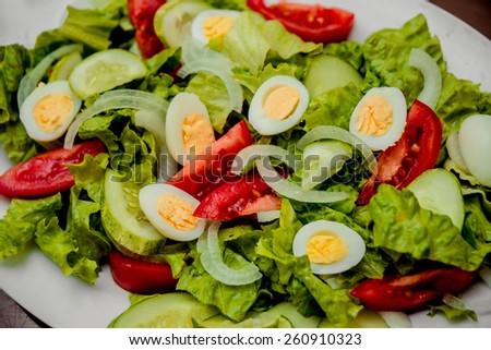 Salad. Lettuce, cucumbers, tomatoes, onions, quail eggs. restaurant - stock photo