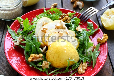 salad of arugula with pear and lemon sauce, food closeup - stock photo