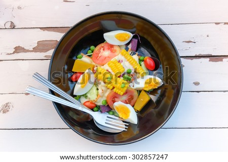 Salad of egg,corn, tomatoes, cucumbers, olives on a plate.Top View. - stock photo
