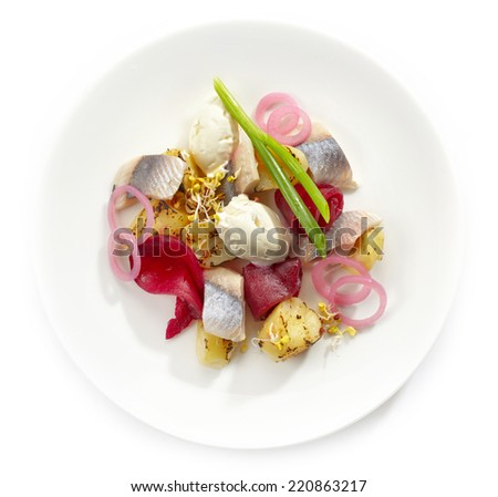 salad of herring and potatoes on white plate isolated on white - stock photo