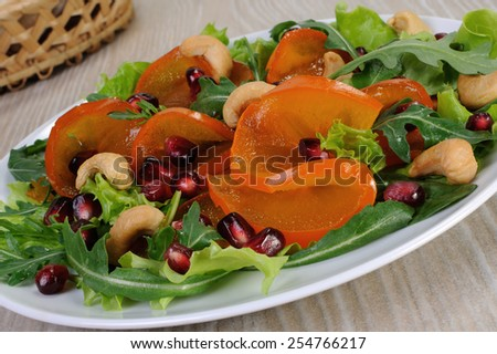 salad of spinach, arugula, lettuce, persimmon, pomegranate and cashews - stock photo