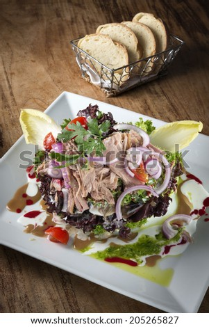 Salad plate with tuna, lollo rosso, chicory, tomatoes, onionsand vinaigrette - stock photo