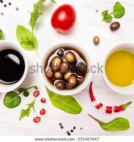 Salad preparation with dressings,olives, wild herbs leaves, chili, oil and tomatoes on white wooden background, top view - stock photo