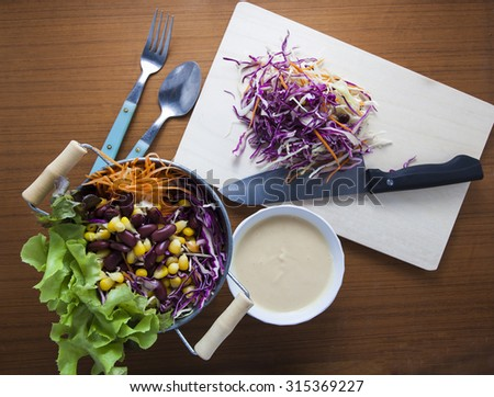 salad top view on wooden background. with carrot, corn, cabbage,violet cabbage, red beans, Butterhead Lettuce - stock photo