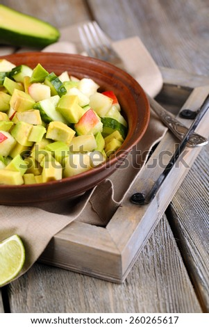 Salad with apple and avocado in bowl on tray on table close up - stock photo