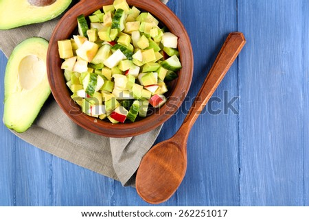 Salad with apple and avocado in bowl with napkin on wooden background - stock photo