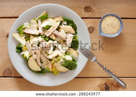 Salad with apple and pork chop, mustard dressing - stock photo