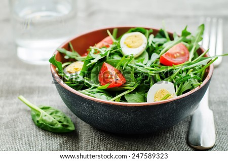 salad with arugula, spinach, tomatoes and eggs. tinting. selective focus - stock photo
