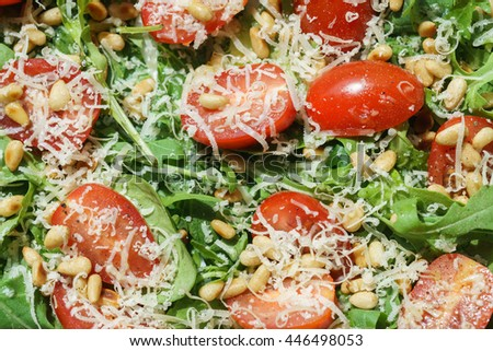 Salad with arugula, spinach, tomatoes, parmesan and pine nuts - stock photo