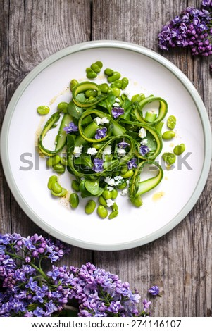 Salad with asparagus ribbons, broad beans and lilac - stock photo