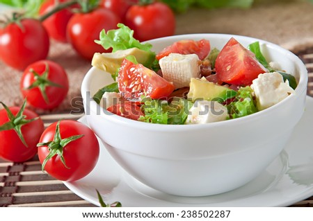 Salad with avocado, cherry tomatoes and mozzarella with honey-bacon dressing - stock photo
