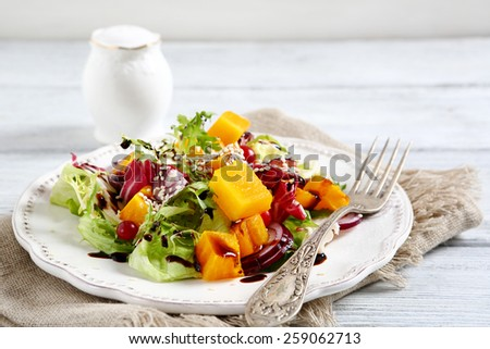 Salad with baked pumpkin on a plate, food - stock photo