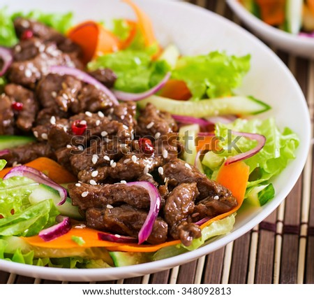Salad with beef teriyaki, carrot, cucumber and lettuce - stock photo