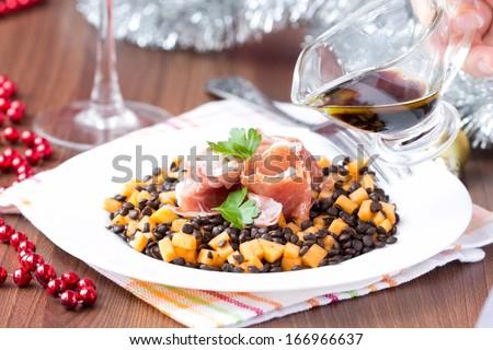 Salad with black lentils, jamon ham, pumpkin, soy sauce, Christmas appetizer - stock photo