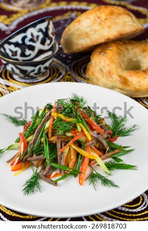 Salad with Boiled beef, fried eggplant and bell pepper, cucumber and tomatoes, garlic, herbs on plate in the oriental style - stock photo
