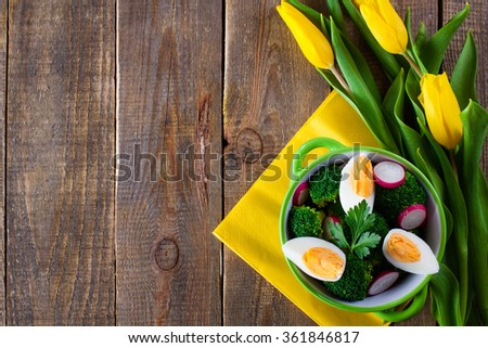 Salad with broccoli, eggs and radishes in a small bowl on wooden background and tulip bouquet, with copy space. - stock photo