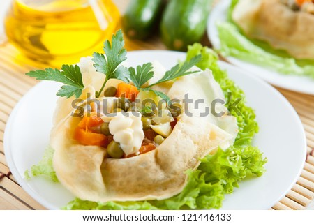 Salad with cooked vegetable and mayo wrapped in a pancakes and lettuce on a plate. Close-up - stock photo
