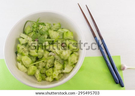 Salad with cucamber and marrow squash with parsley onion next to japanese chopsticks on a green background served - stock photo