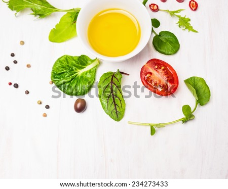 Salad  with dressing,olives and tomatoes on white wooden background, top view - stock photo