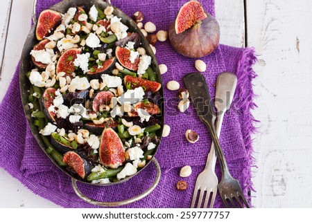 Salad with figs, green beans, goat cheese and hazelnuts. - stock photo