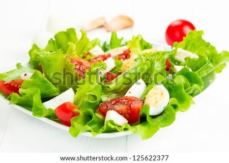 salad with fresh tomatoes, mozzarella cheese and quail eggs - stock photo