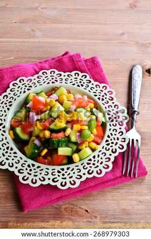 Salad with fresh vegetables in a ceramic dish. - stock photo