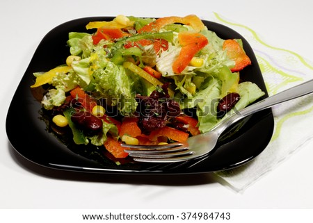 Salad with fresh vegetables on black plate with fork - stock photo
