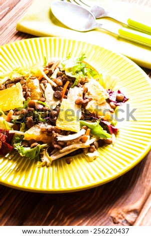 Salad with lentils, carrot, orange and green leaves - stock photo