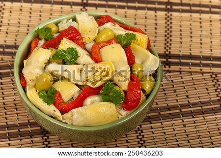 Salad with Marinated Roasted Red Peppers, Artichokes, Olives and Basil Dressing. Selective focus. - stock photo