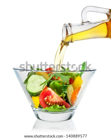 Salad with olive oil pouring from a bottle on white background. With clipping path - stock photo