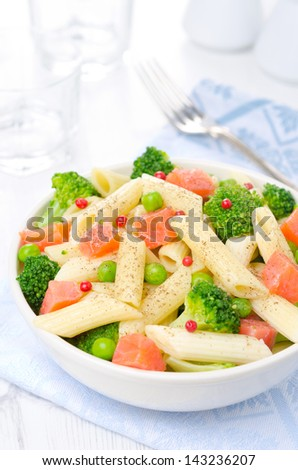 salad with pasta, smoked salmon, broccoli and green peas in a white bowl vertical - stock photo