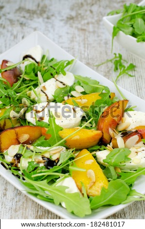 Salad with peach, rocket and mozzarella - stock photo