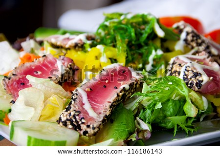 Salad with pieces of medium-rare grilled tuna - stock photo
