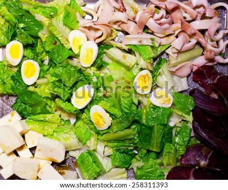 Salad with quail eggs, cheese, lettuce and basturma - stock photo