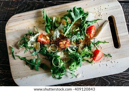 Salad with sesame seeds, arugula and tomato, arugula salad with tomatoes and parmesan, salad on a wooden board, salad on a brown background, salad of arugula - stock photo