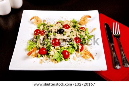 Salad with shrimp, tomatos and sauce served in restaurant - stock photo