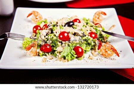 Salad with shrimp, tomatos and white sauce served in restaurant - stock photo