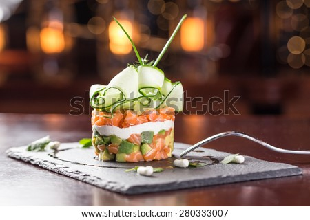 Salad with smoked salmon and cucumber on wooden table - stock photo