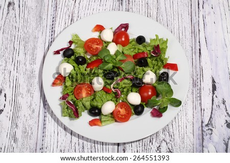 Salad with tomatoes, Mozzarella, olives, cabbage and ruccola - stock photo