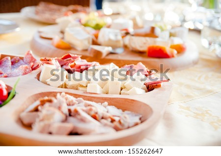 Salami, cheese and prosciutto appetizer on late evening lunch - stock photo