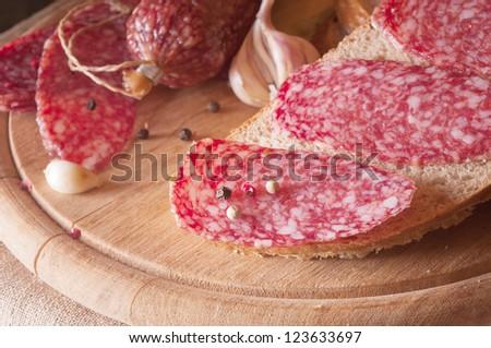 salami close up on a wood board - stock photo