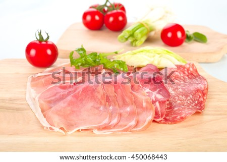 Salami, ham, serrano ham and tomatoes on a plate. - stock photo