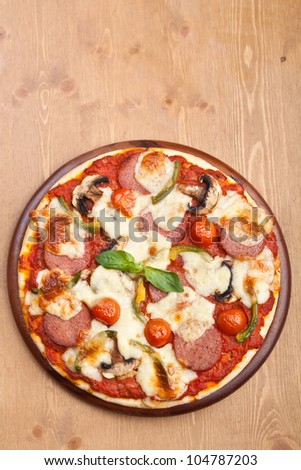 salami, mushroom and vegetable pizza with ingredients on cutting board - stock photo