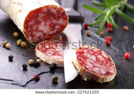 Salami sausage sliced on dark slate background. Selective focus on salami slice. - stock photo