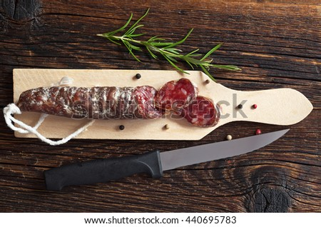 Salami sausages sliced, small cutting board and knife on old wooden table, top view - stock photo